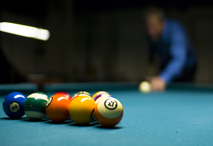 Man breaking, first shot of pool game.